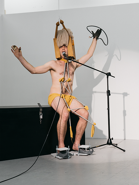 Person speaking into microphone wearing no clothes apart from structure on head and fabric wrapped around legs