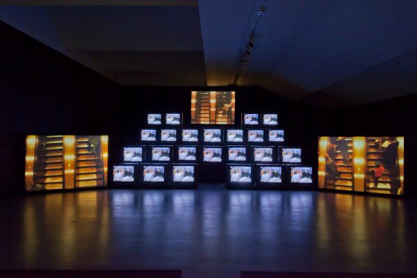 Stacks of television screens showing the same image in a dark room