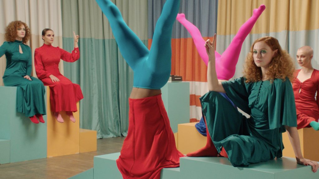 Two people doing handstands in neon coloured tights surrounded by sitting people with raised index fingers