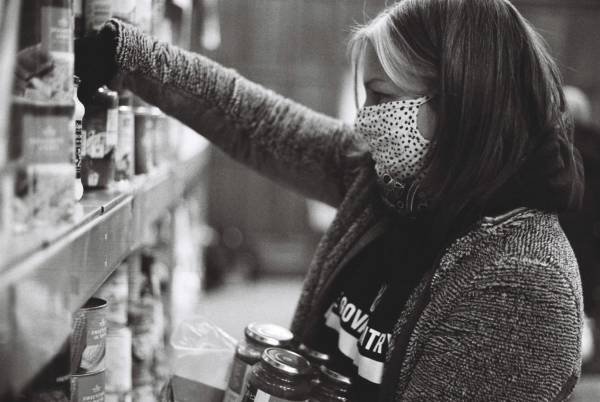 A person with midlength hair and highlighted streaks framing their face, and who is wearing a spotted mask, is stacking shelves with jars